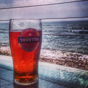 A pint of Gold Star beer by the sea in Haifa