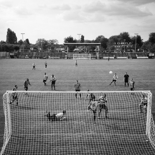 A Tooting & Mitcham United defender clears off the line during their pre-season friendly with Kingstonian