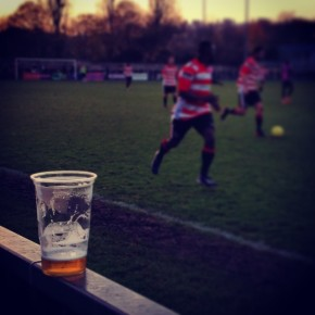 A drink rests on the terrace at Dulwich Hamlet against Kingstonian