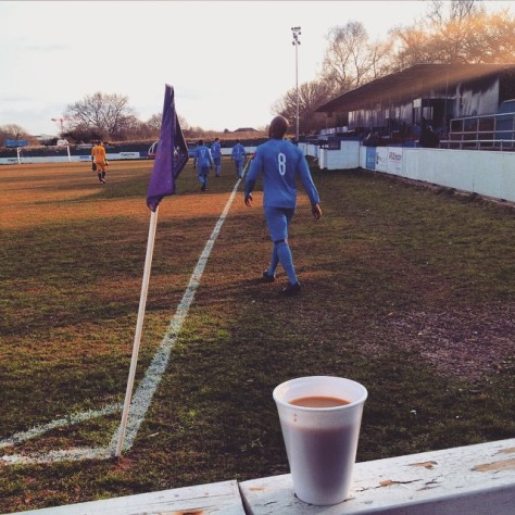 A cup of tea rests on the terrace wall as Redbridge players come out for the second half of their game versus Tilbury