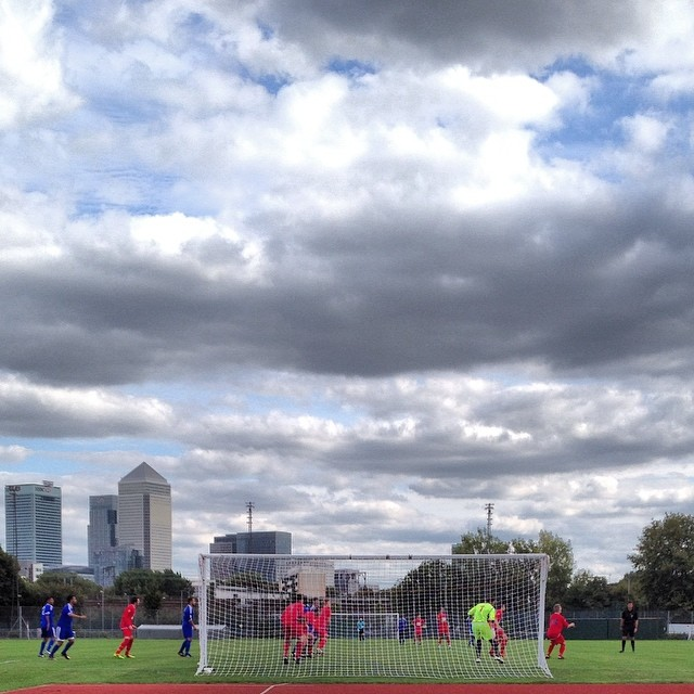 FC Clacton defend a Sporting Bengal United corner in front of a backdrop of Canary Wharf in their FA Cup extra preliminary round match