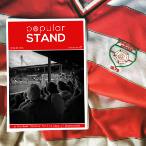 Front cover of issue 85 of popular STAND fanzine on top of a vintage Doncaster Rovers home shirt