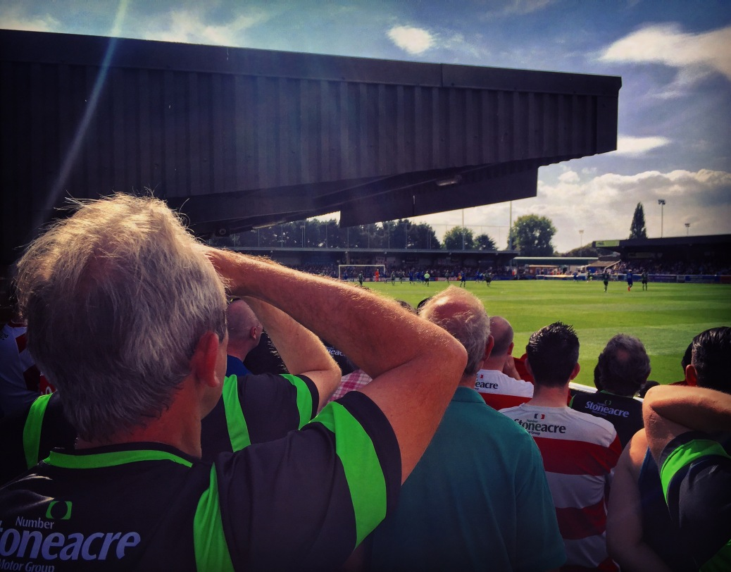 Doncaster Rovers fans try to watch on in bright sunshine during their team's 2-0 defeat to AFC Wimbledon at Kingsmeadow