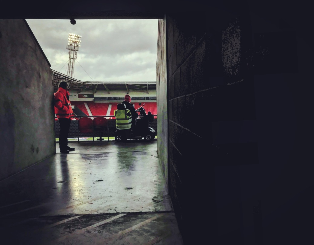 A steward and a Doncaster Rovers supporter watch the rain fall at the Keepmoat Stadium during half-time in Rovers' 4-0 home defeat to Fleetwood Town
