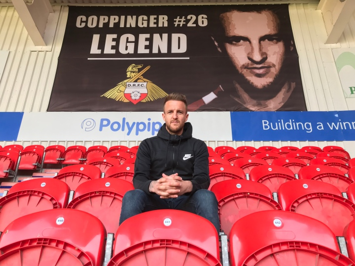 James Coppinger sits in the seats at Doncaster Rovers Keepmoat Stadium in front of a banner celebrating him
