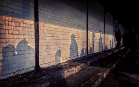Shadows of spectators cast against the back wall of the covered terrace at Buxton's Silverlands during the Boxing Day Peak Derby in the Northern Premier League Premier Division