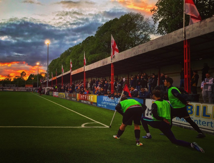 The sun sets as substitutes warm up during the Isthmian League Premier Division Play-Off Semi-Final at The War Memorial Sports Ground