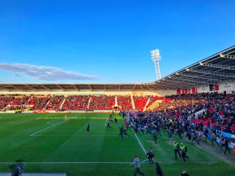 Doncaster Rovers fans stream onto the field at full-time in the League One fixture, to celebrate securing a play-off spot
