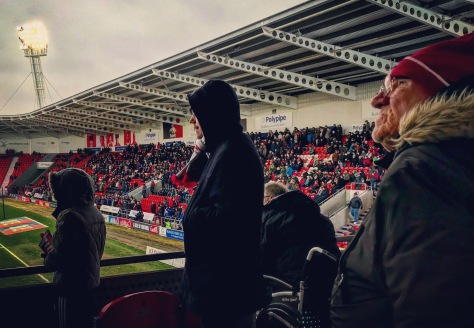 Supporters look on during the closing stages of the League One tie at Keepmoat Stadium