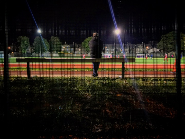 A spectator sits on a steeplechase hurdle to watch the Southern Counties East League Division One match at Ladywell Arena