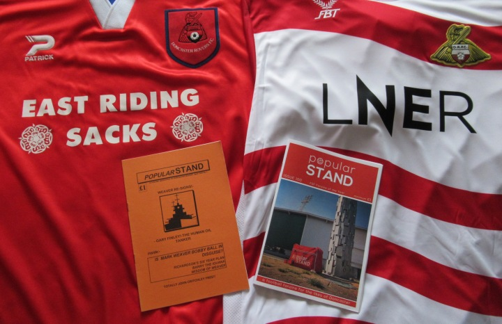 Issues 1 and 100 of popular STAND fanzine pictured with the Doncaster Rovers shirts of the time