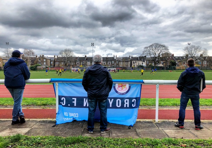 A Croydon supporter with flag, watches his team win at Lewisham Borough