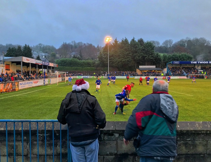 A fan in a santa hat watches the Boxing Day derby between Matlock Town and Buxton