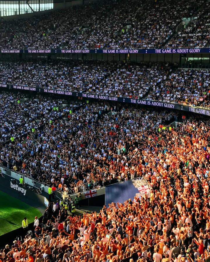 The sun shines on celebrating Newcastle United supporters at the Tottenham Hotspur Stadium