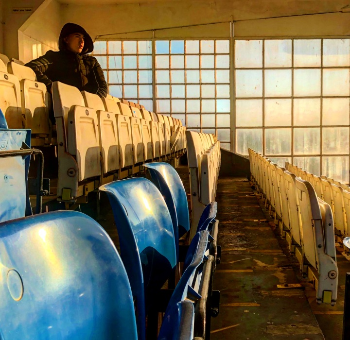 A supporter watches a match from the grandstand at Maurice Rebak Stadium