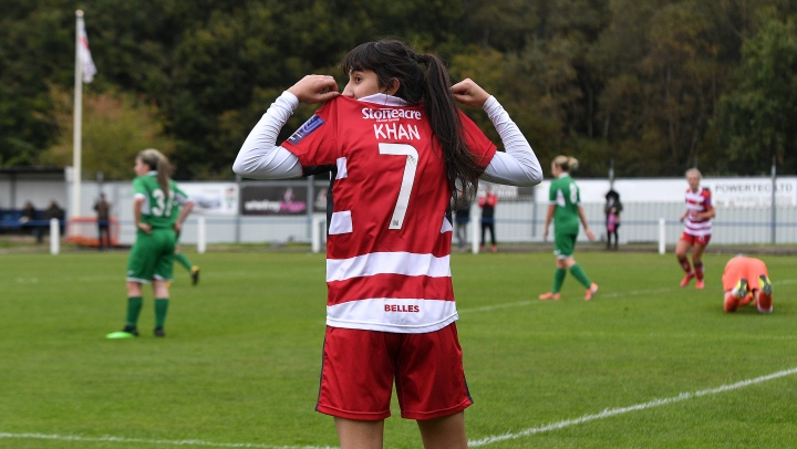 Nadia Khan of Doncaster Rovers Belles shows her shirt number and name in celebration of scoring a goal for the club